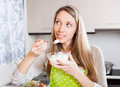 Housewife in apron eating cottage cheese smiling home kitchen Stock Image