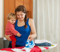 Housewife with baby ironing  at home Royalty Free Stock Photo