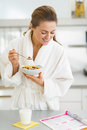 Housewife in bathrobe having breakfast and reading magazine happy young healthy Royalty Free Stock Photo