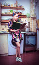 Housewife with book and carcass of a hen in hands Stock Photo