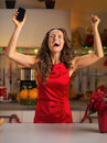 Housewife with cell phone rejoicing happy young in christmas decorated kitchen Royalty Free Stock Photo