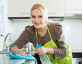 Housewife cleaning furniture in kitchen Royalty Free Stock Photo