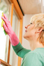 Housewife cleaning her windows in rubber gloves Stock Photos