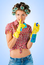 Housewife with cleaning product and a secret on blue background Royalty Free Stock Photography