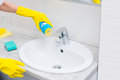 Housewife cleaning a white hand basin Royalty Free Stock Photo