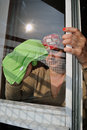 Housewife cleaning a window at home in a sunny day during spring cleaning Royalty Free Stock Image