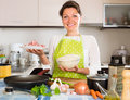 Housewife cooks rice with meat at domestic kitchen Royalty Free Stock Image