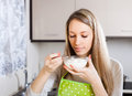 Housewife eating cottage cheese in apron in home kitchen Royalty Free Stock Photography