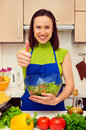 Housewife holding bowl of fresh salad and showing thumbs up Royalty Free Stock Photo