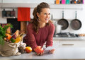 Housewife holding grocery shopping checks happy young in kitchen Royalty Free Stock Images