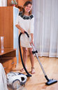 Housewife hoovering surfaces at home ordinary in casual dress Royalty Free Stock Images