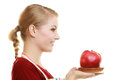 Housewife in kitchen apron offering apple healthy fruit Royalty Free Stock Photo