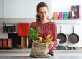 Housewife with local market purchases in kitchen portrait of young Stock Image