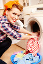 Housewife putting the laundry into the washing machine closeup of cheerful Royalty Free Stock Photo