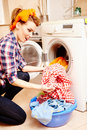 Housewife putting the laundry into the washing machine portrait of attractive Stock Image