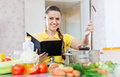 Housewife reads cookbook for recipe happy young at domestic kitchen Stock Images