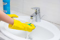 Housewife rinsing off a sponge for cleaning the bathroom under the running water from the hand basin close up view of her gloved Stock Image