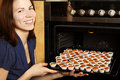 Housewife taking cupcakes from oven Stock Photos