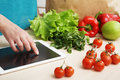 Housewife uses a tablet computer in the kitchen young woman following recipe cooking vegetables on digital online food Royalty Free Stock Images