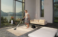 Housewife with vacuum cleaner in a room Royalty Free Stock Photography