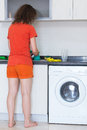 Housewife washing dishes barefoot indoor Stock Image