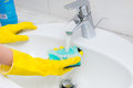 Housewife washing the hand basin in the bathroom Royalty Free Stock Photo