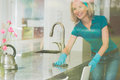 Housewife wipes counter top Royalty Free Stock Photo