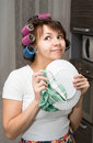 Housewife wipes plate and dreams in kitchen Royalty Free Stock Photo