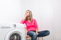 Housework young woman doing laundry putting colorful garments into the washing machine shallow dof color toned image Royalty Free Stock Image