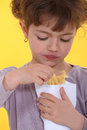 How does it taste little girl isn t sure she likes what she s eating Stock Photos