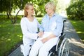 How are you pretty nurse talking to senior patient in a wheelchair in park Stock Image