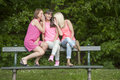 Hree young female friends seated on a bench outdoors three in the parc Stock Photography