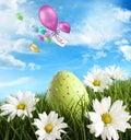 Huevo de Pascua en la hierba con las margaritas Imagen de archivo libre de regalías