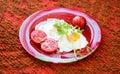 Huevos fritos con las verduras en una placa roja Imagen de archivo libre de regalías