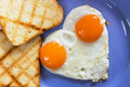 Huevos fritos en forma de corazón Imagen de archivo libre de regalías