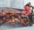 Huge bull spit cooked skewered in the mechanized rotisserie gigantic Stock Photo