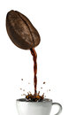 Huge coffee bean with hole pouring coffee into a mug splashing at white background clipping path included Stock Images