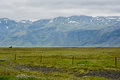 Huge green empty field with view to mountain and small house Royalty Free Stock Photo