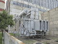 Huge industrial high voltage substation power transformer on rai rails at plant Stock Photo