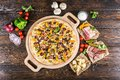 Huge pizza with sausage, pickled cucumber, bacon on a round cutt Royalty Free Stock Photo