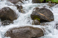 Huge wet rocks in a stream of boiling water. Royalty Free Stock Photo