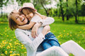 Hugging happy mother and daughter for a walk in the park On the green lawn.