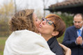 Hugging and kissing the bride with groom in background Royalty Free Stock Photo