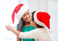 Hugging mother and daughter in santa helper hats family children christmas x mas happy people concept Stock Image
