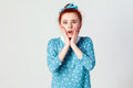 Human face expressions and emotions. Redhead young girl screaming with shock, holding hands on her cheeks. Royalty Free Stock Photo