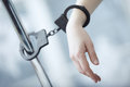 Human hand bounded to the metal pole by handcuffs Stock Photo