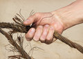 Human hand compresses old steel cable on a background of sand Stock Photos