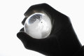 Human hand with cotton gloves gripping glass globe Royalty Free Stock Photo
