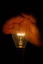 Human hand holding a light bulb to conserve energy in darkness Stock Photo