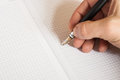 Human hand holding pen and writing something in notebook Royalty Free Stock Photo